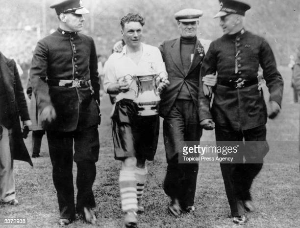 Starling the captain of Sheffield Wednesday's FA Cup winning side is escorted off the pitch with the trophy Sheffield Wednesday beat West Bromwich...