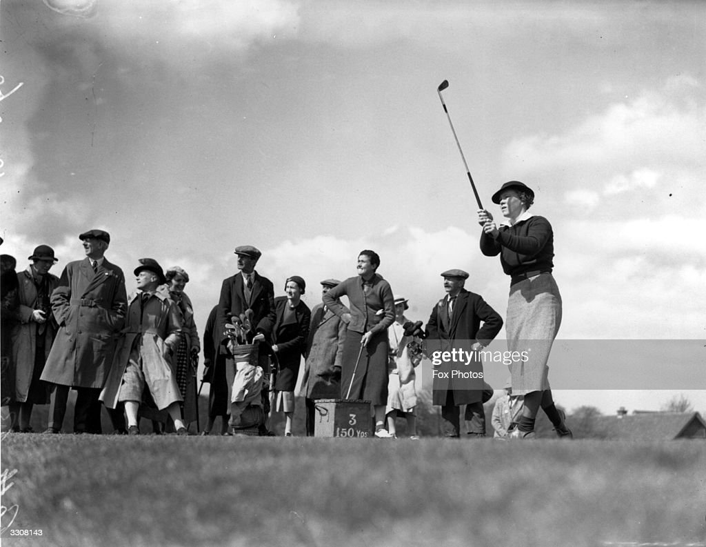US golfer Patty Berg in action during a game, watched by a group of spectators.
