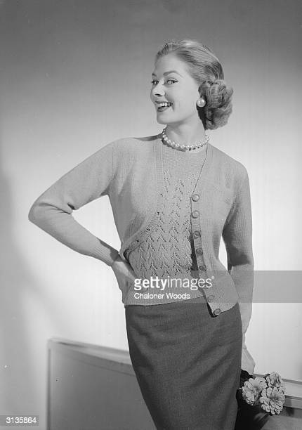 A model happily shows off a jersey twin set of a blouse and cardigan