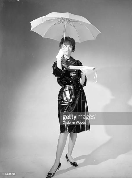 A woman in a dark plastic raincoat demonstrates a pocket umbrella in its opened and retracted forms