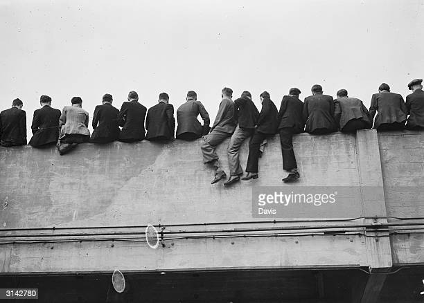 A row of spectators watching the match between Arsenal and Portsmouth from a convenient vantage point overlooking the Arsenal ground
