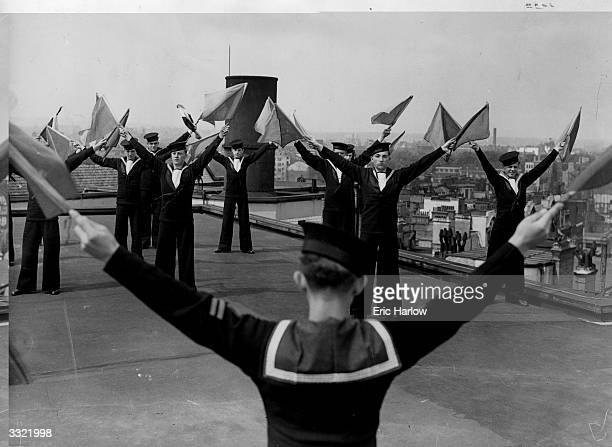 Members of the St Clements Danes Sea Cadets having their weekly semaphore signalling practise on the roof of Brittanic House, Moorgate, London.