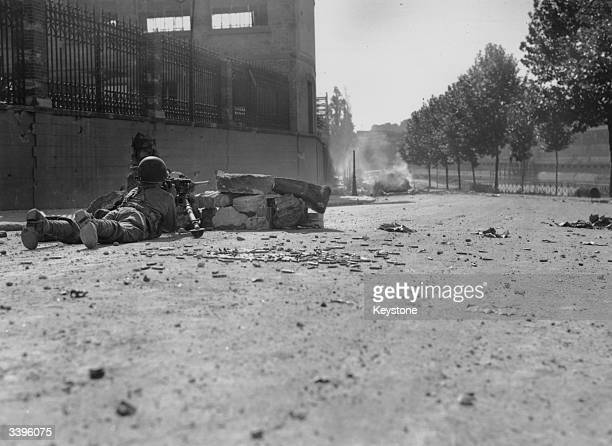 A French soldier firing from behind a small stone barricade in a Paris street