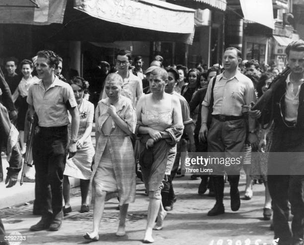 Two women, partially stripped, their heads shaved and with swastikas painted on their faces, are marched barefoot down the streets of Paris, to shame...