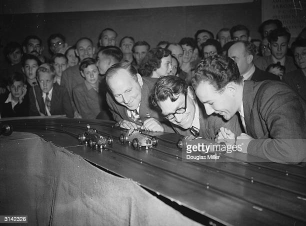 Motor racing stars Reg Parnell Bob Gerard and Stirling Moss eagerly participate in the first Miniature Grand Prix Motor Car Race at the New Royal...