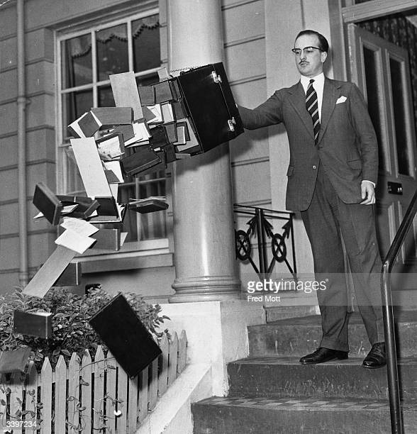 Inventor John H T Rinfret demonstrating his antibandit bag To foil thieves the chain is pulled and the bottom of the case falls out so the contents...