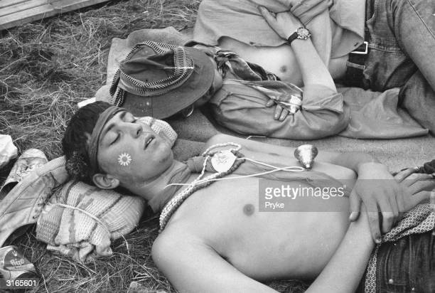 Two young men sleeping on the grass at a Festival of Flower Children held in Woburn Park seat of the Duke of Bedford