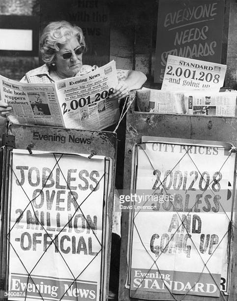 A paper seller reads the news as headlines proclaim that unemployment in Britain has overtaken the two million mark the largest number since the...