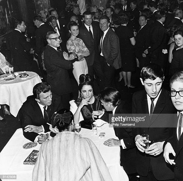 Actors Elizabeth Taylor and Richard Burton attend a smart function at Gstaad ski resort in the company of Mr and Mrs John Sullivan