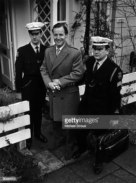British light entertainer Nicholas Parsons with Securicor guards after a threat to kidnap him