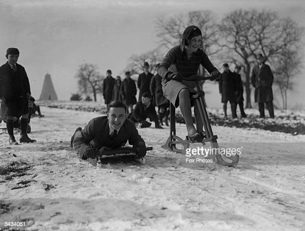 A snowcycle races a toboggan on a wintry slope in Epping Forest
