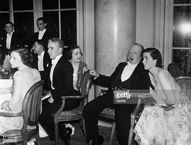 British politician and later prime minister Winston Churchill joins comedian Charlie Chaplin at a party celebrating the opening night of Chaplin's...