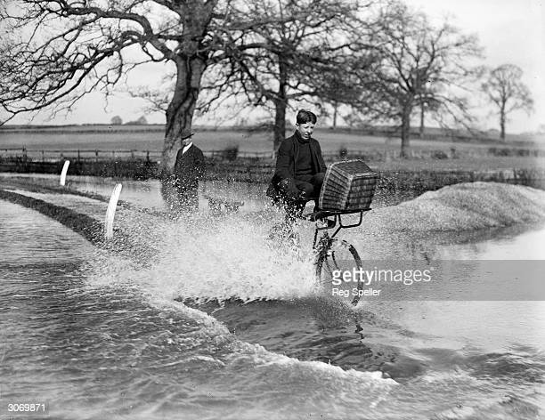 A cyclist lifts up his legs to avoid the splashing as he pedals down a flooded lane in the Thames Valley