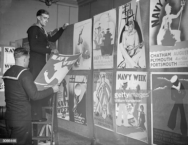 Sailors arrange a selection of the submissions for a poster competiton organised for Navy Week at Admiralty House in Whitehall, London. A prize is...