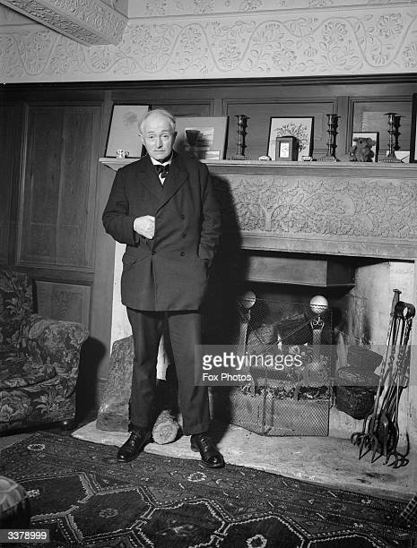 English poet laureate and novelist John Masefield standing by his home fireplace