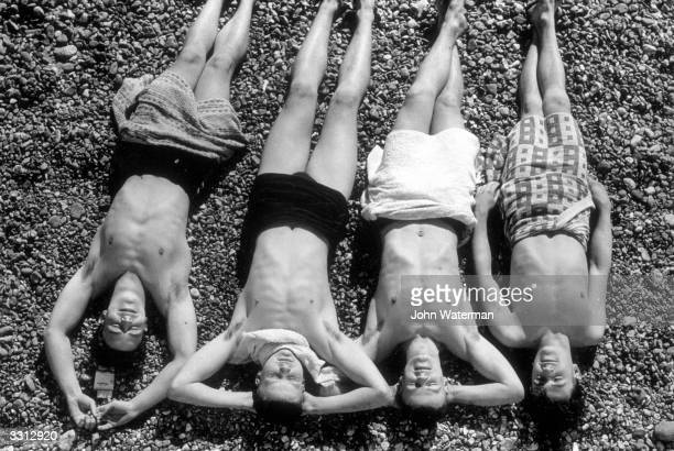 A group of young men sunbathing on Brighton beach