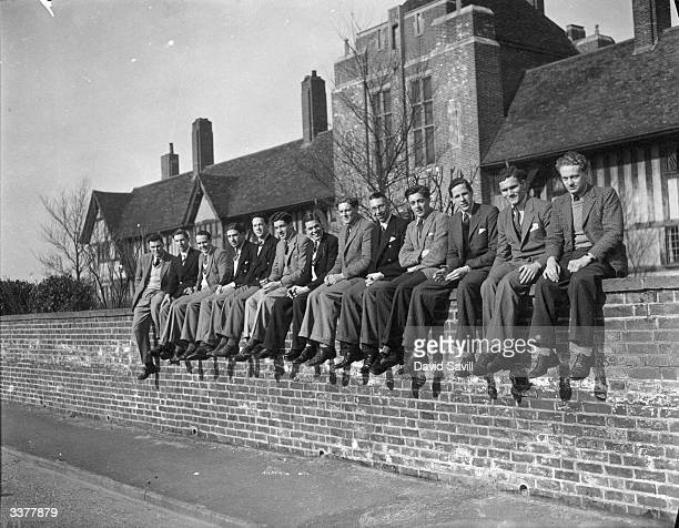 The Cambridge University rowing crew sitting on a wall at Thorpeness in Suffolk