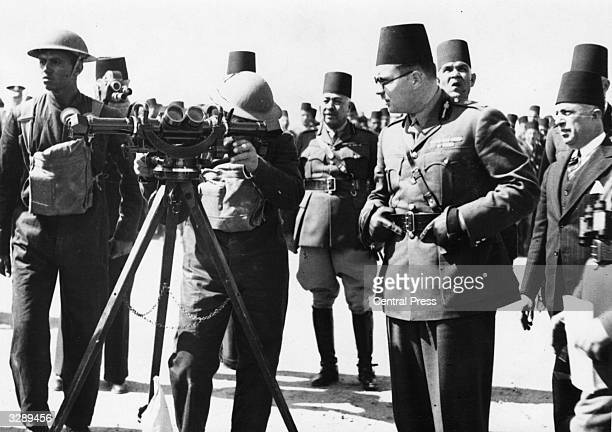 King Farouk of Egypt makes a close examination of a rangefinder during exercises of the Egyptian army artillery