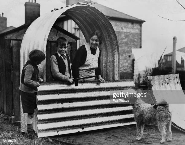 Mrs Ferguson of Manchester, England, and her children enjoy the first free steel air raid shelters to be delivered to the north of England.
