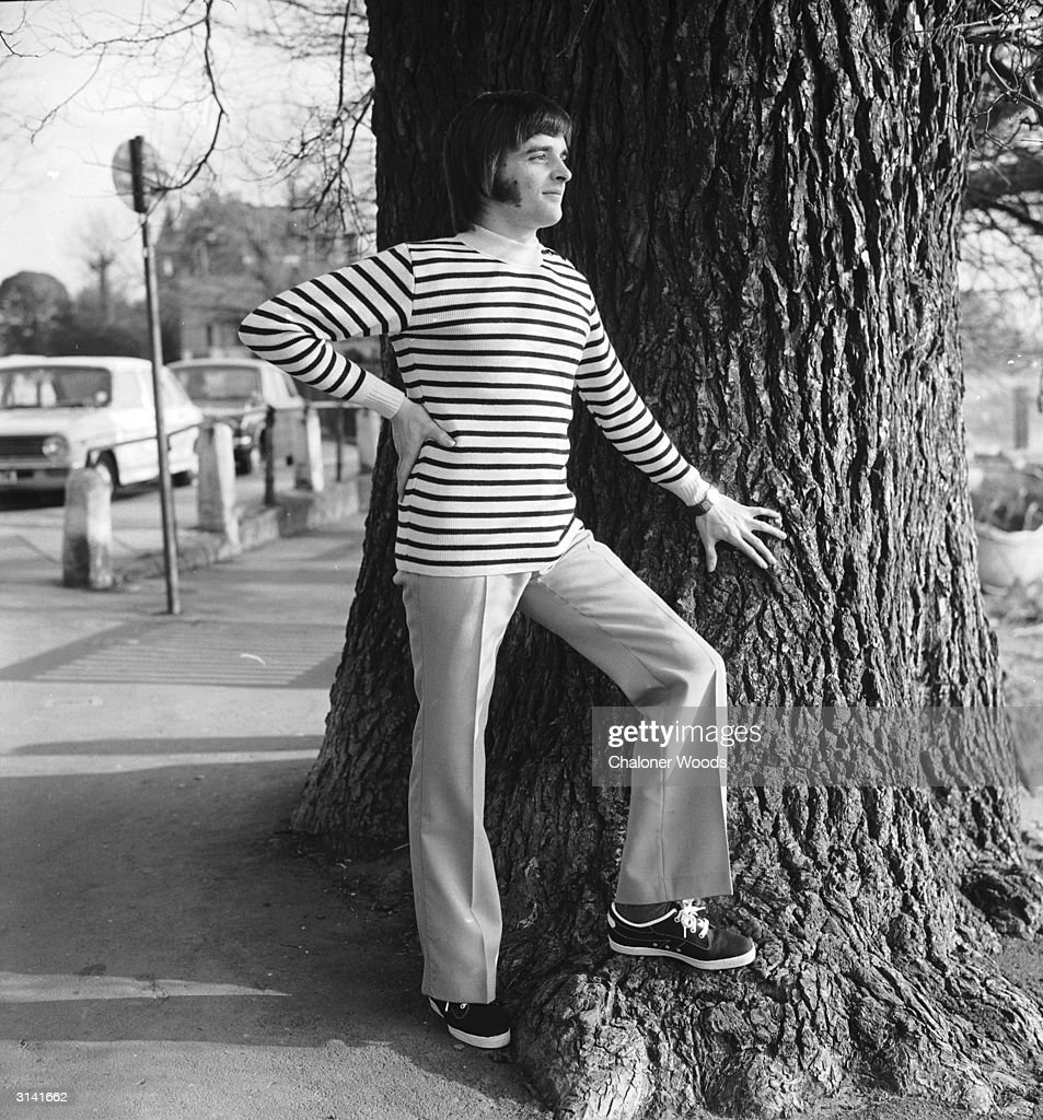 A trendy young man sporting extensive sideburns models a Gallic-style striped jersey and trainers.