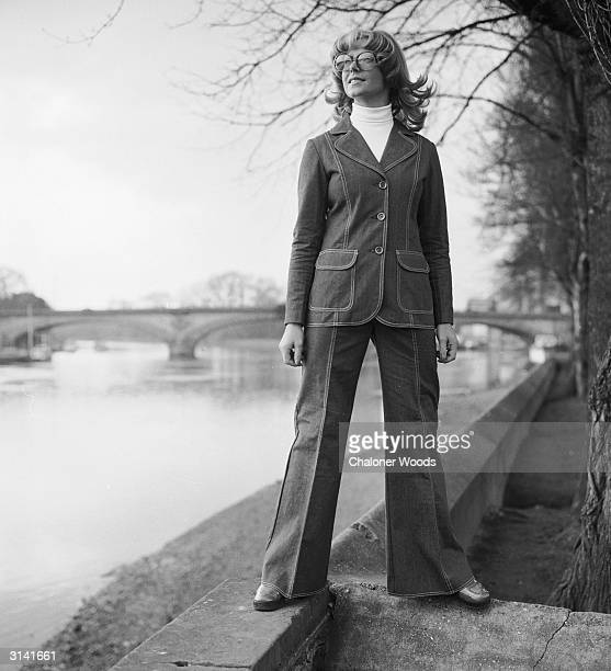 A woman stands confidently on the banks of a river sporting a flared denim suit over a white poloneck jumper
