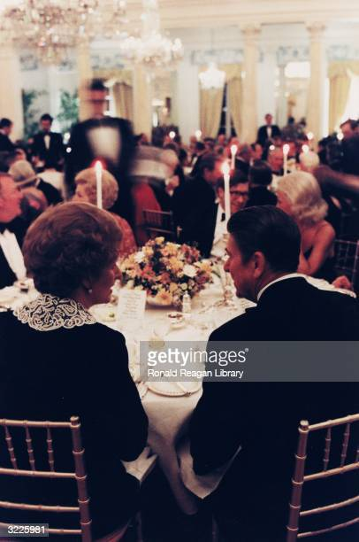 British prime minister Margaret Thatcher sits beside US president Ronald Reagan at a table with their backs to the camera at a British Embassy dinner...