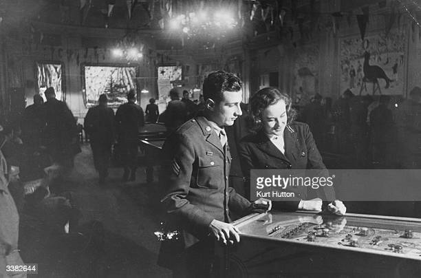 American soldiers playing pinball at Rainbow Corner the American Servicemen's Club in London Original Publication Picture Post 1887 Inside Rainbow...