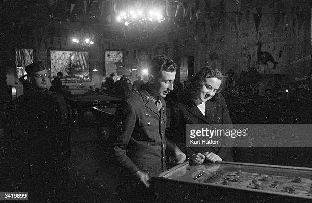 An American GI playing on the pinball machine inside Rainbow Corner the American Red Cross club for servicemen in London's Piccadilly Original...
