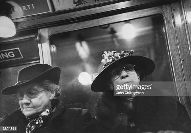 Passengers travel on a London Underground train Original Publication Picture Post 5185 Rush Hour To Midnight pub 1951