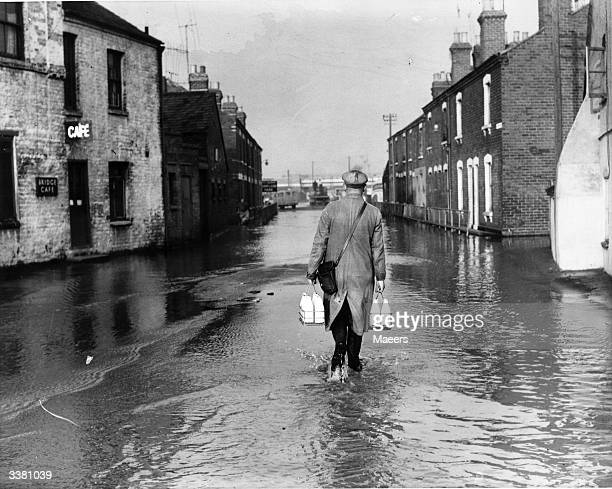 A milkman trudges along a submerged street in Gloucester undeterred by the flooding of the River Severn into the Severn Valley caused by heavy rain