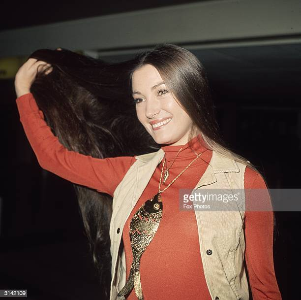 English actress Jane Seymour shows off her famously long dark hair upon arrival at London Airport Around her neck is a large fish pendant