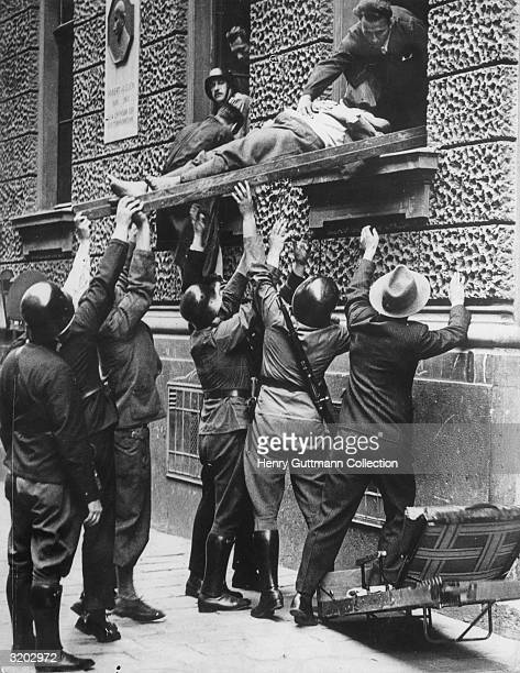 A badly wounded Nazi being lifted out of the window of the Vienna Broadcasting Station on the day Dollfuss was murdered after their broadcast hoax...
