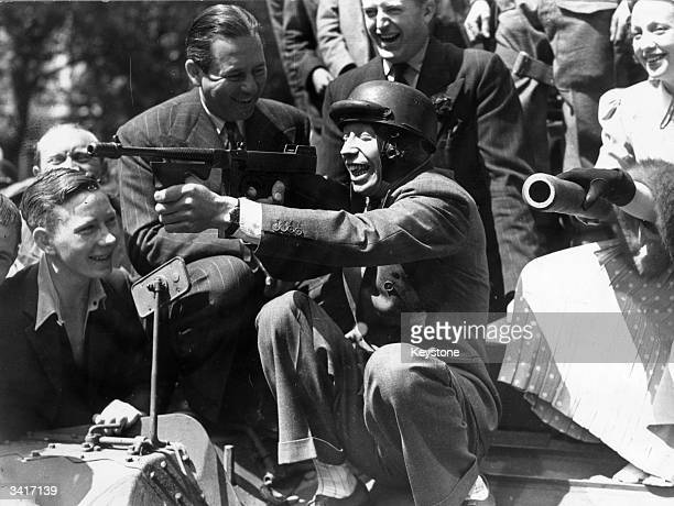 British comedian George Formby enjoying himself with a tommy gun before his Tank Show at the Odeon Leicester Square London