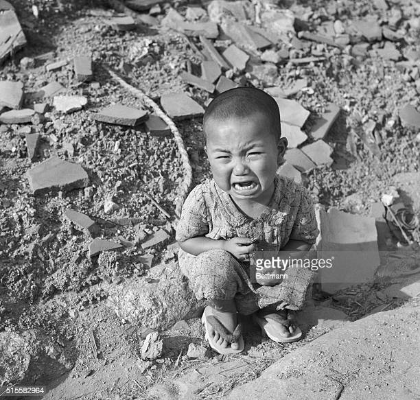 Japanese child sits crying in the rubble of Hiroshima a year after the city was devastated by the world's first atomic bomb attack, on August 6,...