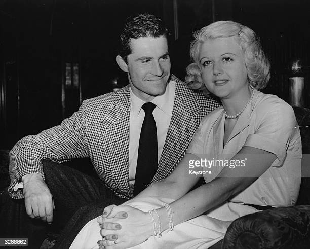 British actress Angela Lansbury with Peter Shaw on their arrival at London Airport before their wedding