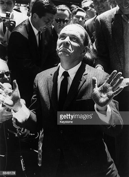 American actor and singer Frank Sinatra with his hands covered in cement, after making an imprint at Grauman's Chinese Theatre, Hollywood.