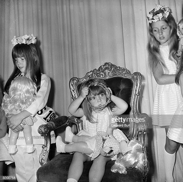 Two and half year old Louise Stewart makes a reluctant Queen as she removes her crown after winning the 'Miss Pears' contest