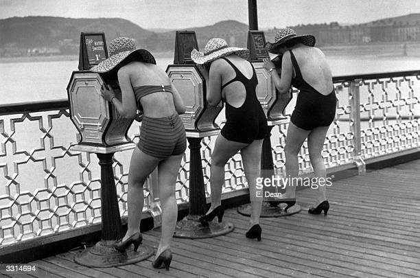 Holidaymakers view 'What The Butler Saw' picture peep shows on the pier at Llandudno North Wales