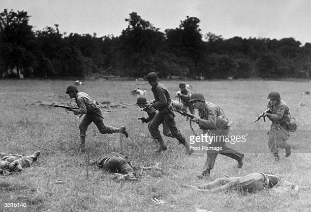 American artillery men in Cherbourg advancing across ground strewn with dead Germans and dead cattle