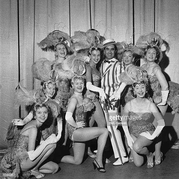 Film star Tyrone Power wearing a straw boater and striped blazer in 'Night of a 100 Stars' at the London Palladium He is surrounded by a group of...