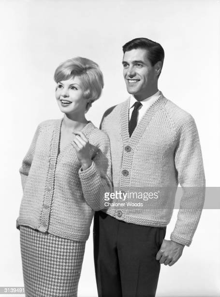 An upbeat, preppie young couple wear matching woollen V-neck cardigans while being amused by a sight unseen.