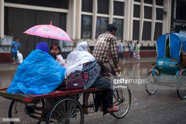 A family in a van covered with polythene and umbrella during rain in Dhaka on 27th June 2015Heavy raining in the city continued for a four...