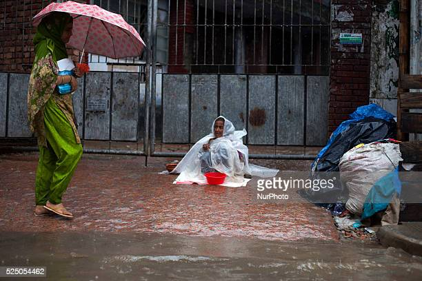 An old women begging on foothpath in waterlogged streets during rain in Dhaka on 27th June 2015Heavy raining in the city continued for a four...