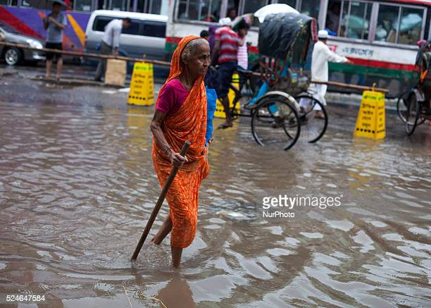 An old women walking on waterlogged streets during rain in Dhaka on 27th June 2015Heavy raining in the city continued for a four consecutive day...