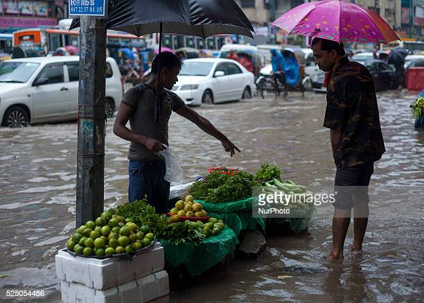 Street hawcker selling vegitables in waterlogged streets during rain in Dhaka on 27th June 2015Heavy raining in the city continued for a four...