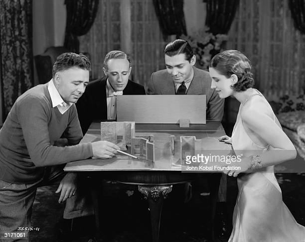 Left to right director Clarence Brown actors Leslie Howard Clark Gable and Norma Shearer with a model of one of the sets for 'A Free Soul'