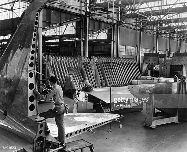 Workmen put the finishing touches to wings and tail fins at the Lockheed Corporation aircraftworks in Burbank, California. The warplanes that they...