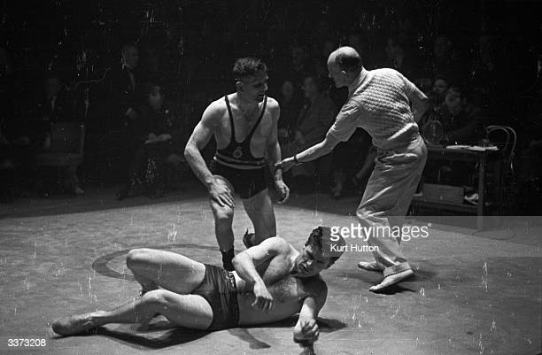 A referee intervenes during a wrestling bout between Dowsett an exChampion of England and Private Constantino Scotti of the USA in the Allied Amateur...