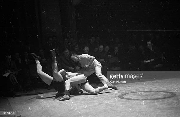 A referee watching the action during a wrestling bout between C T Balaof Britain and Eric Fincus of Palestine in the Allied Amateur Wrestling...