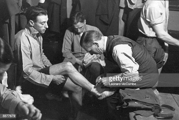 Star football player and RAF corporal Stanley Matthews receives treatment in the RAF team changing room Original Publication Picture Post 1401 The...